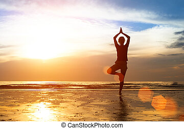 Silhouette of a young woman practicing yoga at sunset.