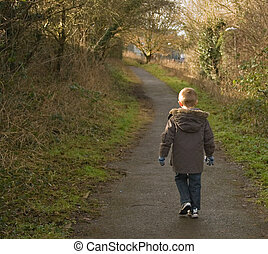 Young boy walking - young boy in a winter coat walking away...