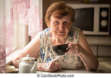 Old woman is drinking tea in his rural home