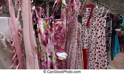 Row of summer dresses for sale - Row of colourful red themed...