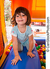 Little girl playing in inflatable bouncing castle - Little...