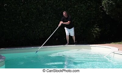 Swimming Pool Cleaning - Footage of man cleaning swimming...