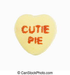 Candy heart on white. - Yellow candy heart that reads cutie...