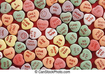 Candy hearts on red - Large group of colorful candy hearts...