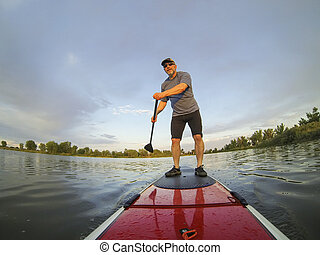 stand up paddling - mature male paddler enjoying workout on...