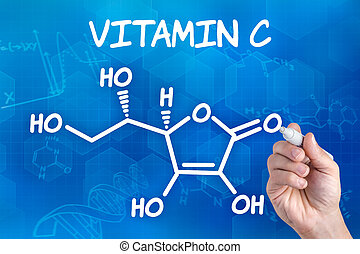 chemical formula of vitamin c - hand with pen drawing the...