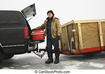 Man going ice fishing. - Caucasian man unloading cooler from...