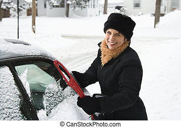 Woman scraping ice. - Caucasian mid adult woman scraping ice...