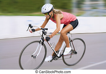 riding fast bike outdoors - young caucasian female woman...