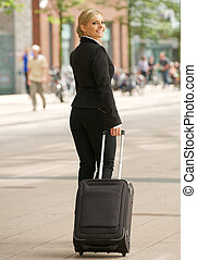 Business woman traveling with suitcase in the city