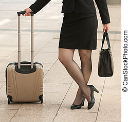 Business woman standing with bags on sidewalk - croped