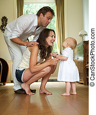 Happy family smiling at baby standing at home - Portrait of...