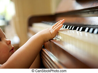 Portrait of a baby playing the piano - closeup portrait of a...