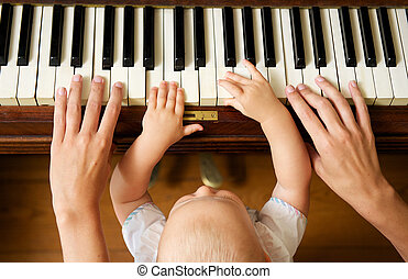 Baby learning to play piano with mother - Closeup portrait...