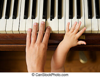 Adult hand playing piano with baby hand - Closeup portrait...