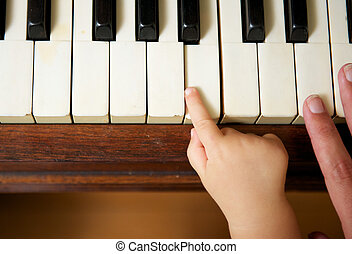 Baby hand playing piano with adult hand - Closeup portrait...