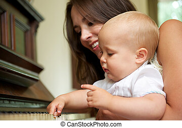 Beautiful woman teaching baby to play piano - Closeup...