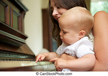 Happy mother teaching cute baby to play piano
