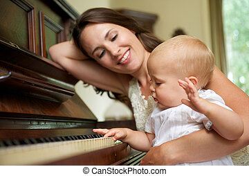 Happy mother smiling as baby plays piano - Portrait of a...
