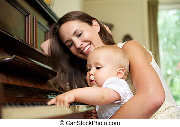Mother smiling as baby plays piano - Portrait of a mother...