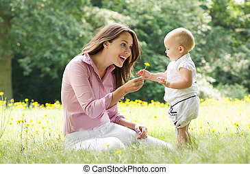 Beautiful mother with baby playing in the park