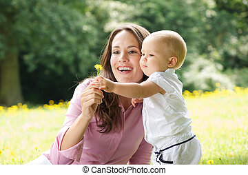 Happy mother and child holding flower in the park