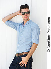 Male fashion model posing with sunglasses outdoors