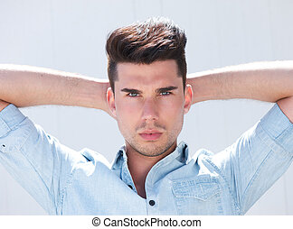 Attractive male fashion model with hands behind head