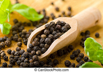 Black Pepper - A scoop of whole black peppercorns against a...