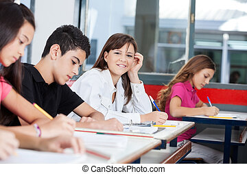 Teenage Girl With Friends Writing At Desk - Portrait of...