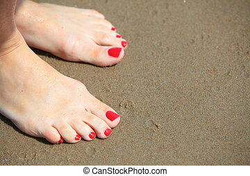 Woman feet with red pedicure relaxing on sand