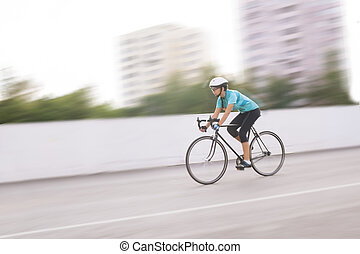 young female athlete racing on a bike. motion blurred image
