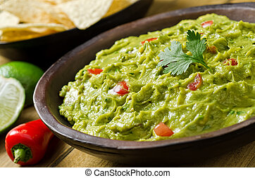 Guacamole Dip - A bowl of creamy guacamole dip with peppers,...