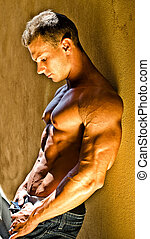 Handsome muscular male bodybuilder leaning against yellow...