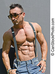 Handsome, muscular bodybuilder with suspenders shirtless -...