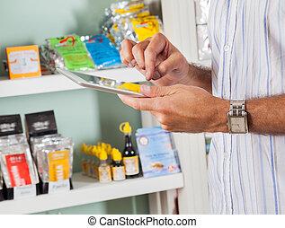 Man Using Digital Tablet In Supermarket