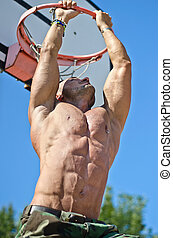 Muscular man hanging from basketball ring - Handsome,...