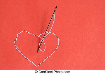 Embroidered heart - Needle standing on red background with...