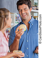 Couple Choosing Cheese At Grocery Store
