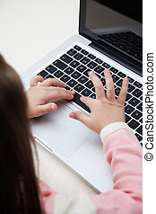 Girl Using Laptop In Classroom - High angle view of little...