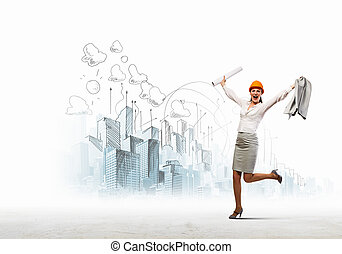 Happy engineer - Young woman engineer in helmet jumping...