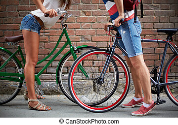 Love among bicycles - Close-up of guy and girl legs with...