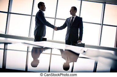 Making agreement - Silhouettes of two businessmen standing...