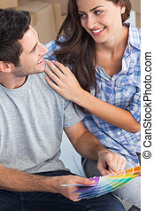 Happy couple looking at color samples to decorate their...