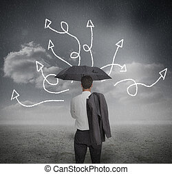 Businessman looking at jumble up arrows holding umbrella in...