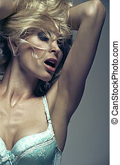 Beautiful woman with long blond hair. Closeup portrait of a fashion model posing at studio.