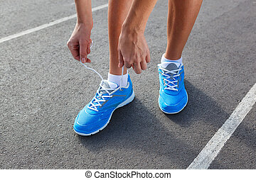 Closeup of Young Woman Tying Sports Shoe - concept image
