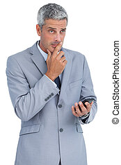 Worried businessman holding his cellphone against white...