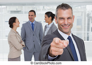 Cheerful businesman in bright office pointing at camera with colleagues on background