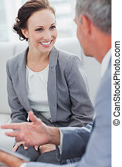 Smiling businesswoman listening to her workmate talking in...